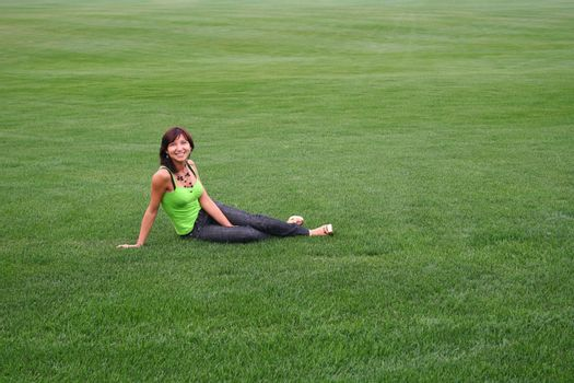smiling girl sits on big lawn covered of young green grass