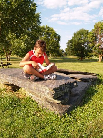 young boy reading a book in a park
