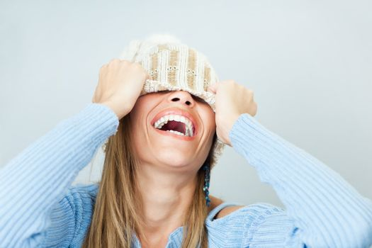 portrait of young woman laughing while covering face with wool hat. Horizontal shape, Copy space