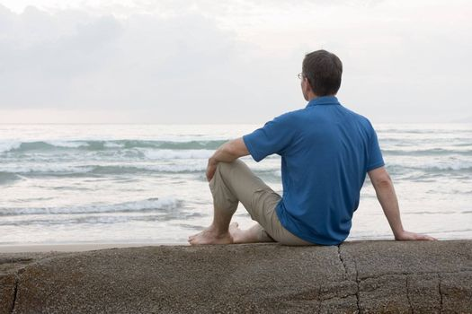 Man sitting on a rock at the sea