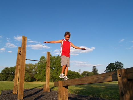 young boy balancing on an outdoor balance beam