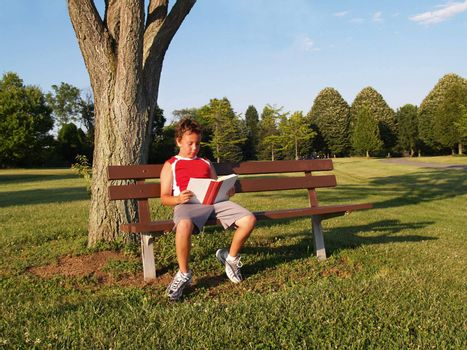 young boy sitting on a park bench and reading a book