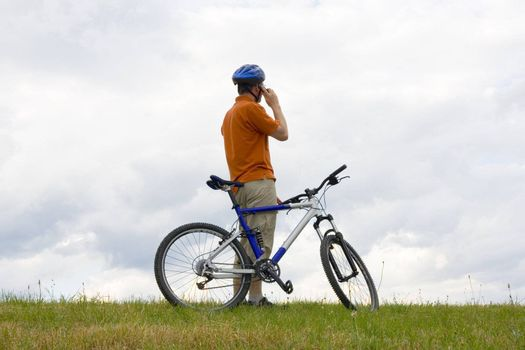 Man with mountain bike in a meadow talking on mobilel phone