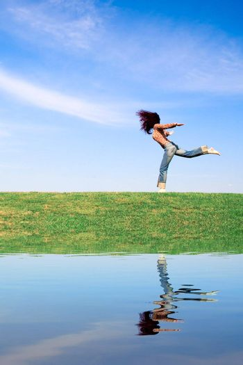 Woman jumping on green field, with water reflection.