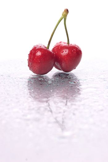 Two cherries, with water droplets, with reflection. Portrait framing.