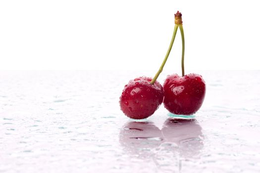 Two cherries, with water droplets, with reflection. Landscape framing.