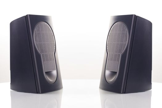 Two computer speakers, with a reflection on white background.