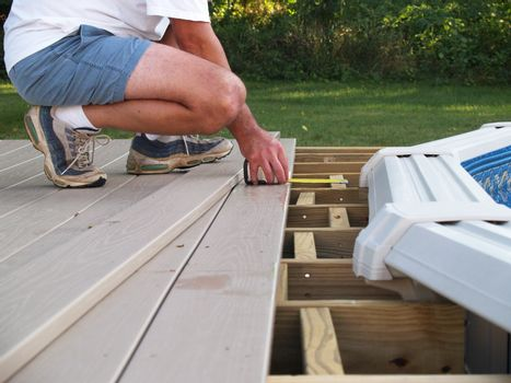 man measuring boards for a new above ground pool deck