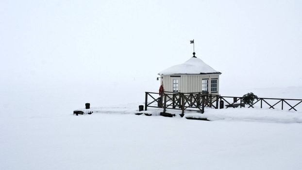 A pier with a house on a foggy winters day