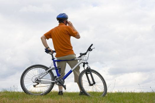 Man with mountain bike on a meadow talking on cell phone