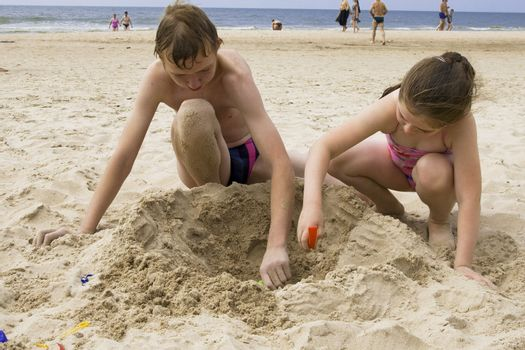 Brothe and sister playing at the beach of Baltic sea