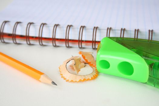 Pencil and sharpner with shavings and a notebook in the background.