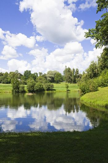 Summer scenery with lake in front, green forest on back with blue sky and clouds