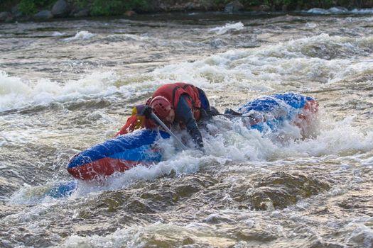 sportsmen on the blue catamaran in the rapid