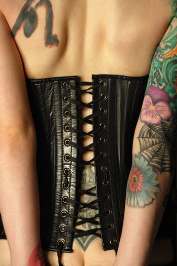 A young slim women with arm and back tattoos dressed in a black leather corset.  Focus is on the middle of corset.