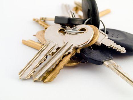 Set of House and Vehicle Keys on White Background