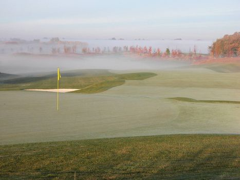 Fog rising from a beautiful golf course on a fall morning