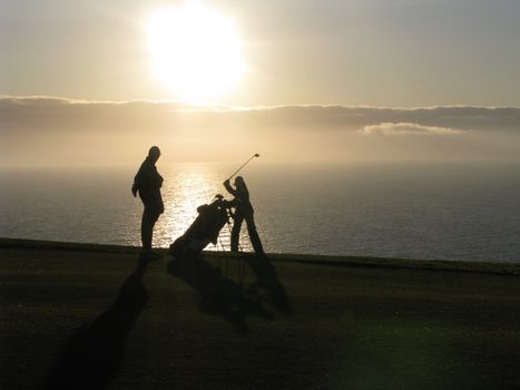 Women golfer in her back swing with her caddy at sunset