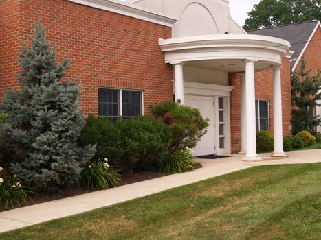 entrance with white columns for a red brick building