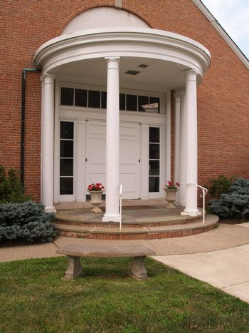 porch with white columns for a red brick building