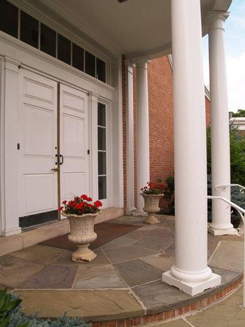 porch with white columns and flowers in an urn