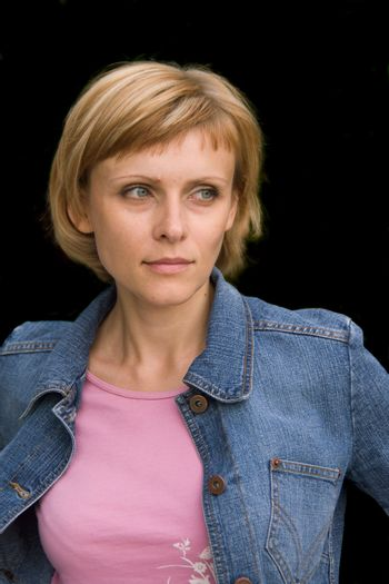 Young woman in a denim jacket isolated on black