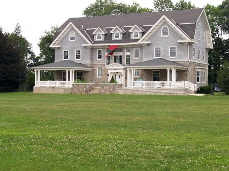 gray clapboard style house with large front porches