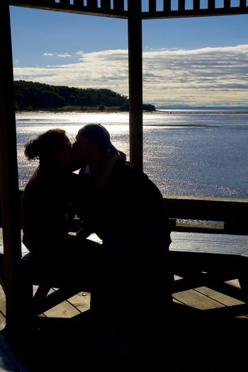 happy couple kissing by the ocean view