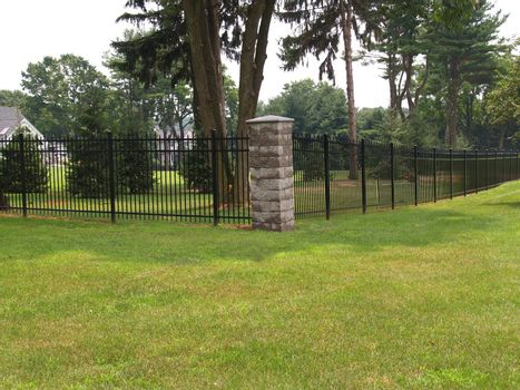 tall black fence and stone corner-piece