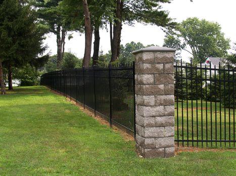 black fence and stone corner-piece around a property