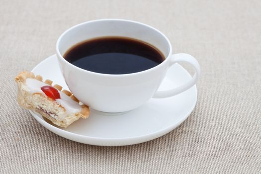 Cup of black coffee with half a small cake