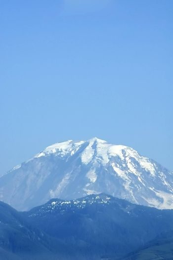 A vertical shot of Mount Rainier's peak from about 50 miles away, in summer.
