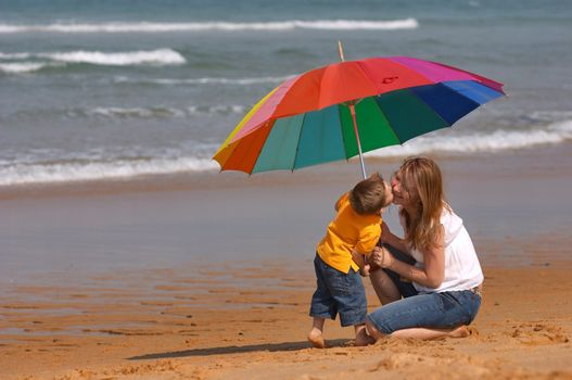 Do not depend on weather conditions. Happy young woman and kid under brightly colored umbrella having fun outdoors.