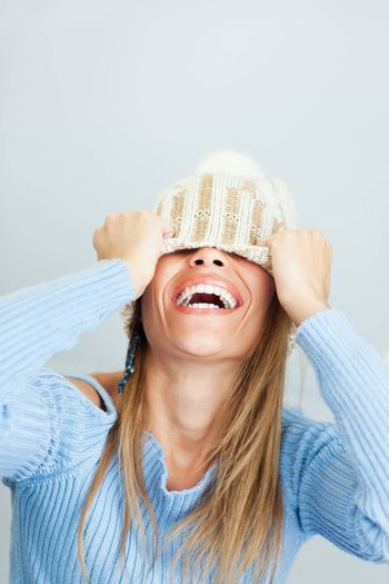portrait of young woman laughing while covering face with wool hat. Vertical shape, Copy space