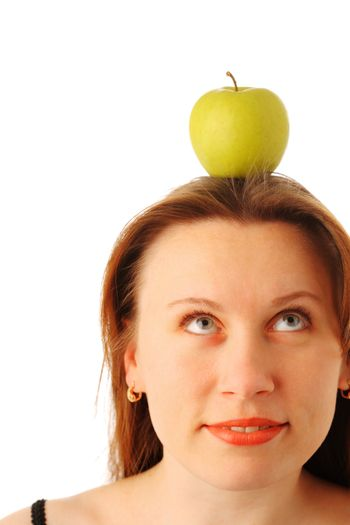 Closeup portrait of a young attractive woman with a juicy green apple on her head, looking up and smiling, isolated over white background