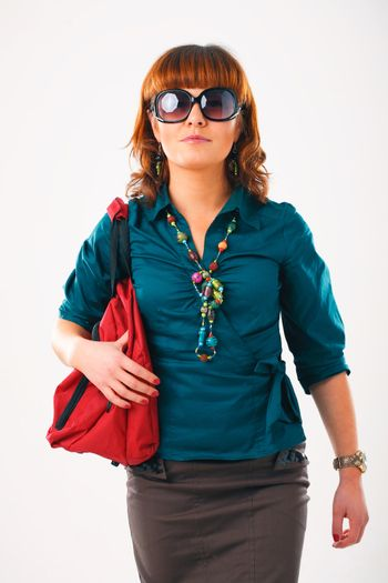 Beautiful young woman in sunglasses with her shopping bags