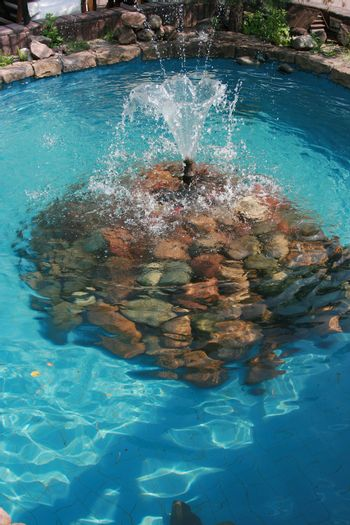 Small freshening fountain in blue pool
