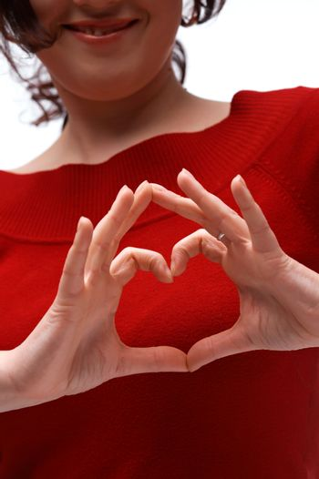 A close up picture of two hands showing a heart symbol