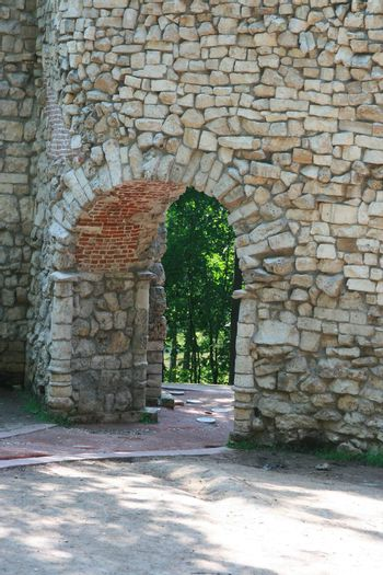 Old stone wall with an arch pass inside