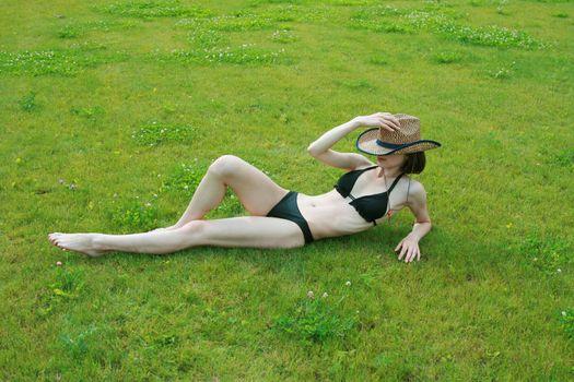 The girl in bikini sunbathes on a green lawn