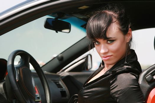 The beautifu girl  poses in the smart car