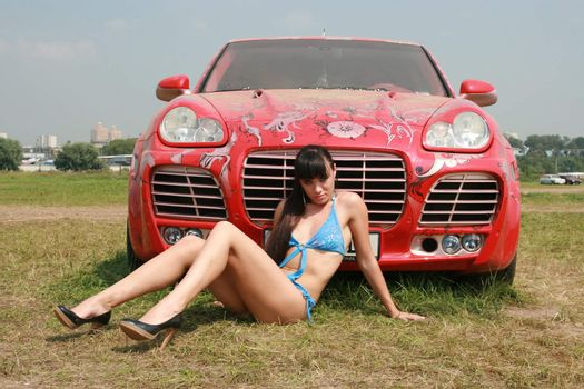 The sexual girl poses near to the smart car
