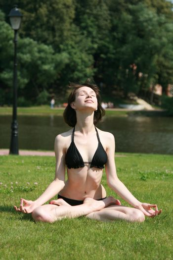 The girl in bikini sits in a pose of a lotus on a lawn