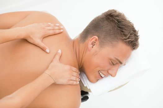 Young blond man enoying massage session in spa resort