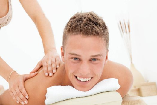 Happy young man enoying massage session in spa resort