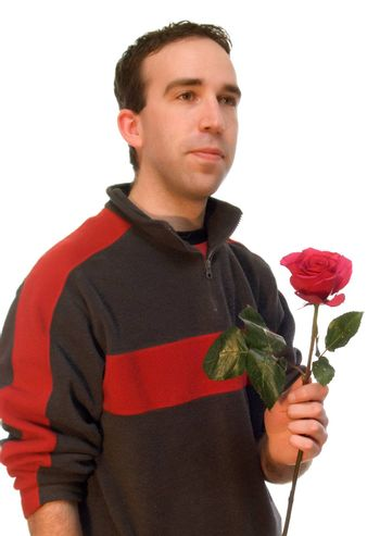 Black and white male holding a rose, isolated against a white background