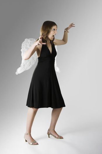 Beautiful woman with angel wings attacking something
