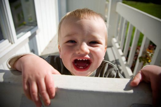 A portrait of a happy toddler boy playing outside in the sun.