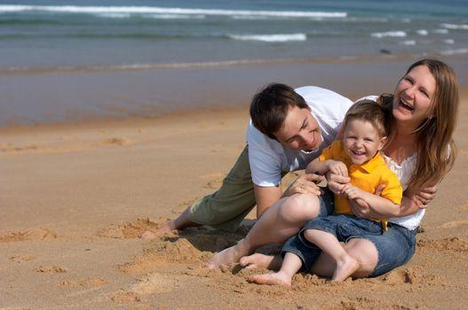 Happy family of three having fun at the beach