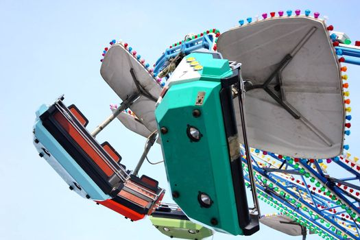 Child attraction in park merry-go-round in front of the blue sky